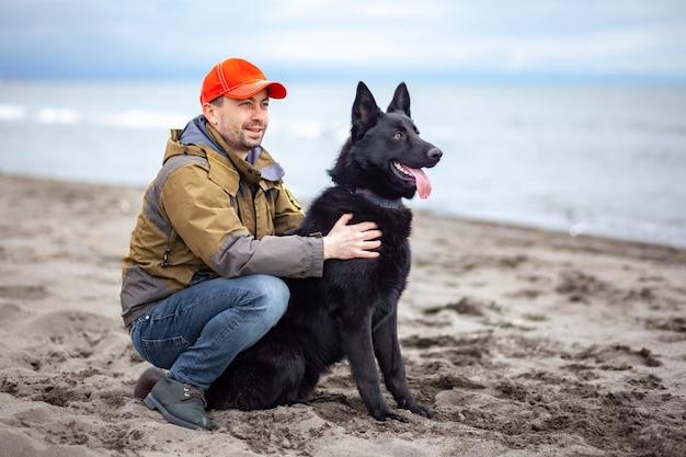 Owczarek niemiecki czarny ze swoim właścicielem na piaszczystym brzegu morza czarnego poti