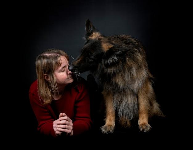 Owczarek niemiecki i kobieta przed czarnym tle