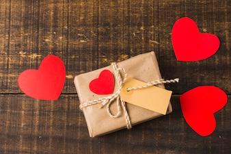 Owinięte pudełko obecne i wycinanka papieru w kształcie serca z pustym tagiem na drewnianym tle