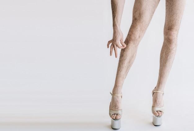 Owłosione nogi na wysokich obcasach w różowe majtki na białym tle