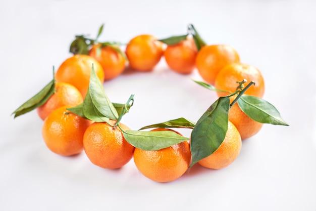 Owoc bożego narodzenia. leżą pomarańczowe świeże mandarynki lub mandarynki z zielonymi liśćmi.