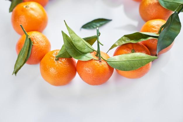 Owoc bożego narodzenia. pomarańczowe świeże mandarynki lub mandarynki z zielonymi liśćmi w papierowej torbie kłamają na białym tle.