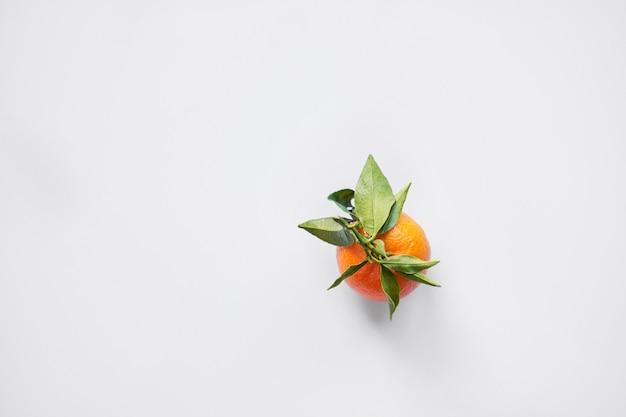 Owoc bożego narodzenia. pomarańczowe świeże mandarynki lub mandarynki z zielonymi liśćmi w papierowej torebce leżą.