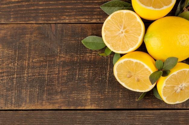 Owoc cytrusowy. świeża cytryna z liśćmi na brązowym drewnianym stole. widok z góry. wolna przestrzeń