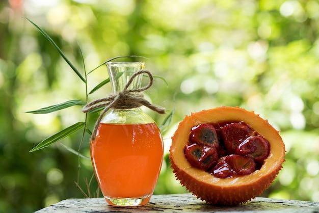 Owoc gac i olej na tle przyrody