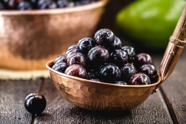 Owoc jaboticaba, egzotyczne winogrono z ameryki południowej, w rustykalnej miedzianej doniczce