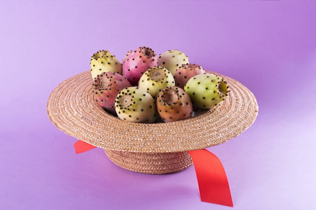 Owoc opuntia w słomkowym kapeluszu na modnym fioletowym tle