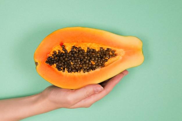 Owoc papai na zielonym tle w rękach kobiety. owoc tropikalny. połowa papai.