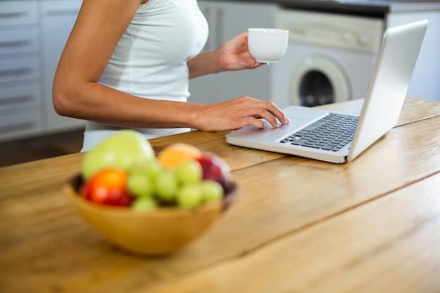 Owoc w pucharze na stole z kobietą pracuje na laptopie