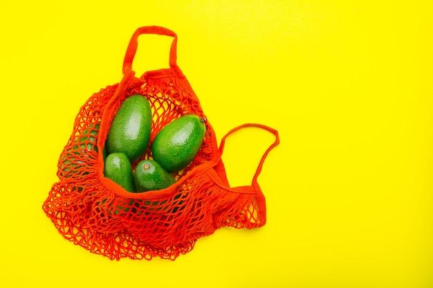 Owoce awokado w czerwonej siatkowej torbie wielokrotnego użytku