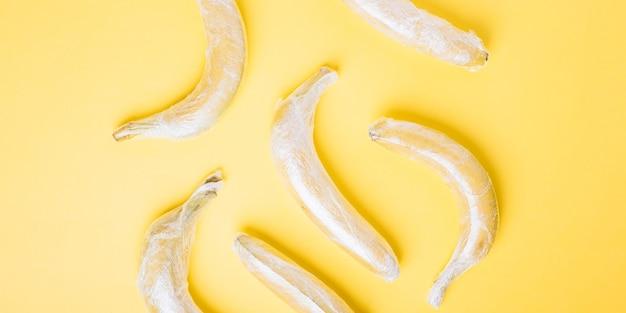 Owoce bananowe zawinięte w elastyczny plastik na żółtej powierzchni