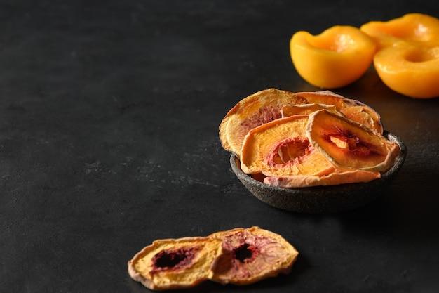 Owoce brzoskwiniowe chipsy w misce na czarno