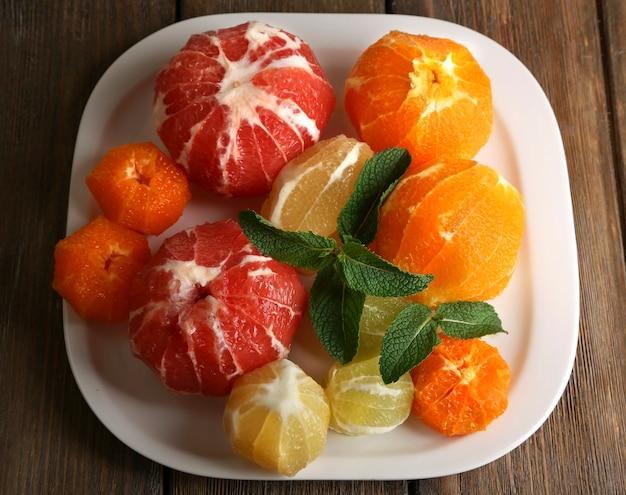 Owoce cytrusowe bez skórki, na talerzu, na powierzchni drewnianej