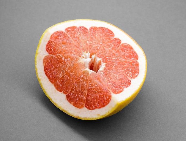 Owoce cytrusowe grejpfruta z pół na białym tle na szary ze ścieżką przycinającą