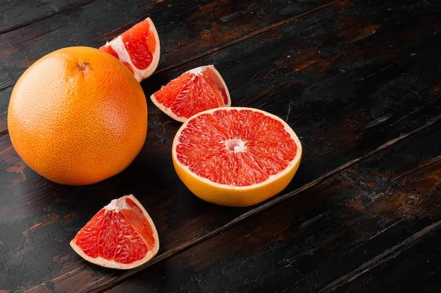 Owoce cytrusowe grejpfruta z pół zestawu, na starym ciemnym tle drewnianego stołu, z kopią miejsca na tekst