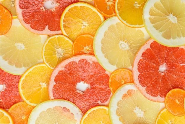 Owoce cytrusowe pokrojone w okrągłe kawałki: pomarańcza, grejpfrut, cytryna, mandarynka. dojrzałe i soczyste owoce, widok z góry
