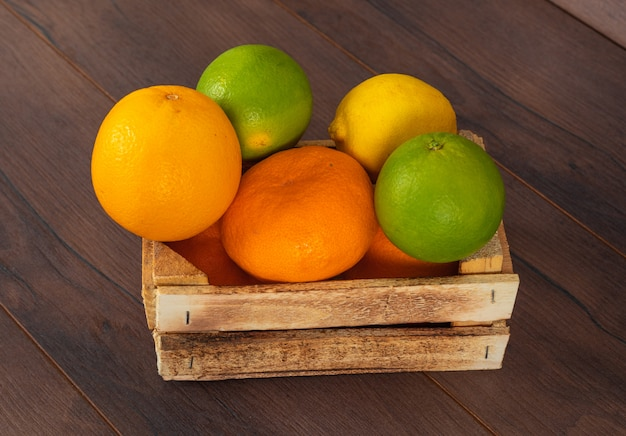 Owoce cytrusowe pomarańczowo-zielona i żółta cytrynowa mandarynka w drewnianym pudełku na brązowo