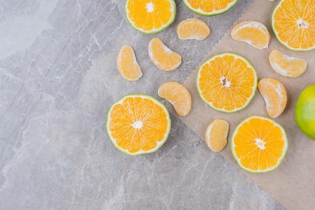 Owoce cytrusowe rozrzucone na kamiennej powierzchni.