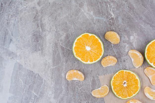 Owoce cytrusowe rozrzucone na kamiennym tle.