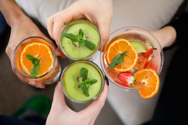 Owoce cytrusowe w szklance wody z bliska. orzeźwiające napoje w dłoni mężczyzny. plastry jasnych świeżych owoców