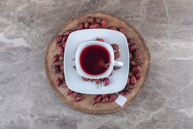 Owoce dzikiej róży i herbata na pokładzie, na marmurowym tle.