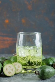 Owoce feijoa i szklanka soku na marmurowym stole.