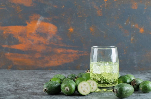 Owoce feijoa i szklankę soku na marmurowym stole. zdjęcie wysokiej jakości