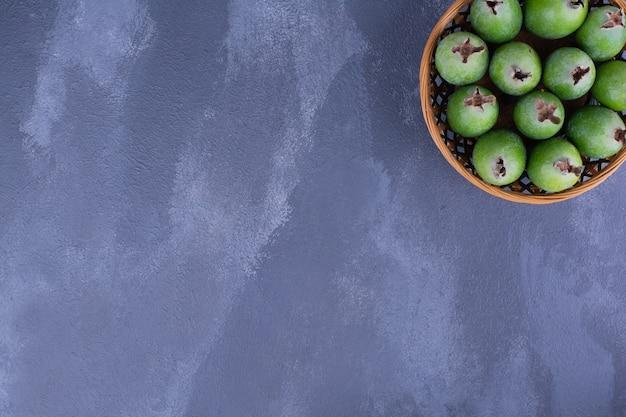 Owoce feijoa w drewnianym kubku na niebieskiej powierzchni