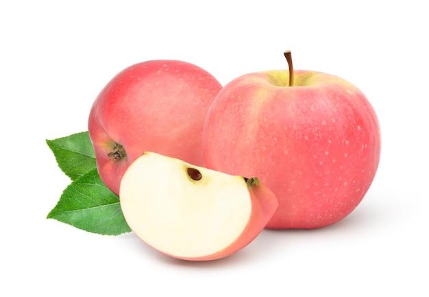 Owoce fuji apple z pokrojone w plasterki i zielone liście na białym tle.