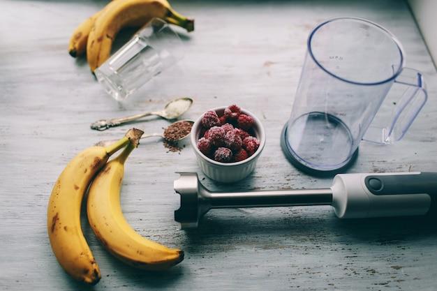 Owoce i blender do robienia koktajli i składników na jasnym tle, widok z góry
