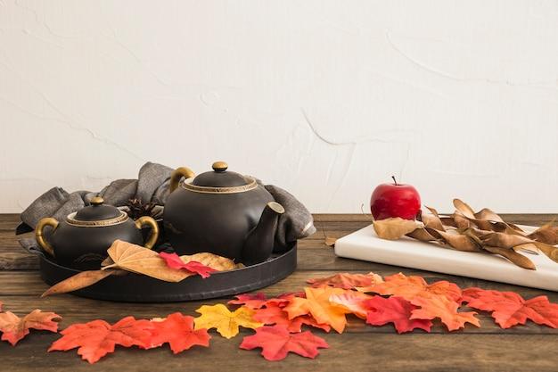 Owoce i notatnik w pobliżu liści i zestaw herbaty