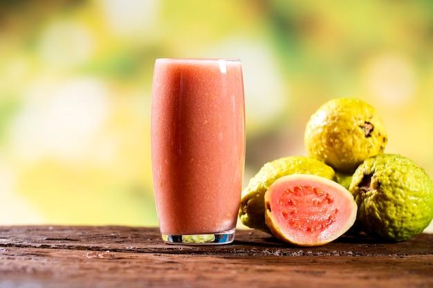 Owoce i sok z czerwonej guawy w szklance na drewnianym stole, odkryty.