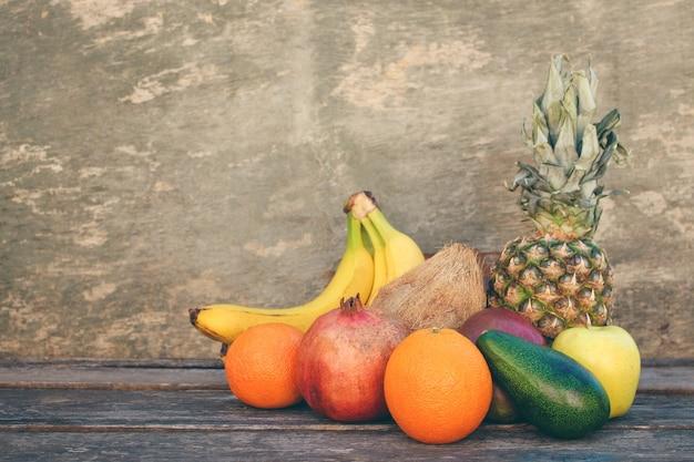 Owoce i warzywa na starym drewnianym tle. stonowany obraz.