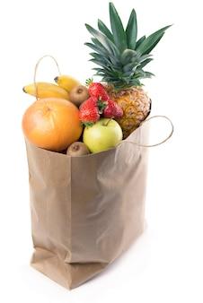 Owoce i warzywa w papierowej torbie na zakupy na białym tle nad białym tle