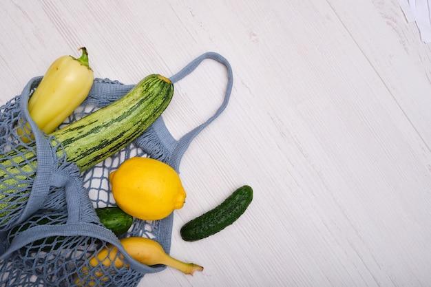 Owoce i warzywa w siatkowej torbie na drewnianym tle