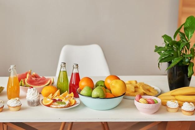Owoce: jabłka, arbuz, ananas, banany, cytryny i pomarańcze na stole