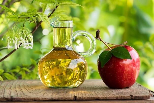 Owoce jabłka i ocet jabłkowy na naturze.
