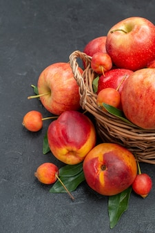 Owoce jabłka wiśnie w koszu nektarynka z liśćmi