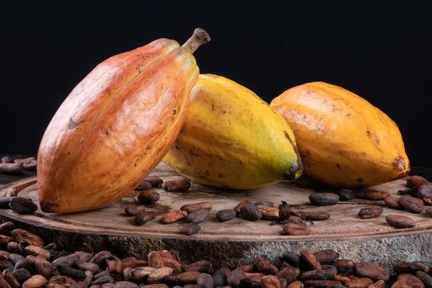 Owoce kakaowe i surowe ziarna kakaowe na stole z czarnym tłem.