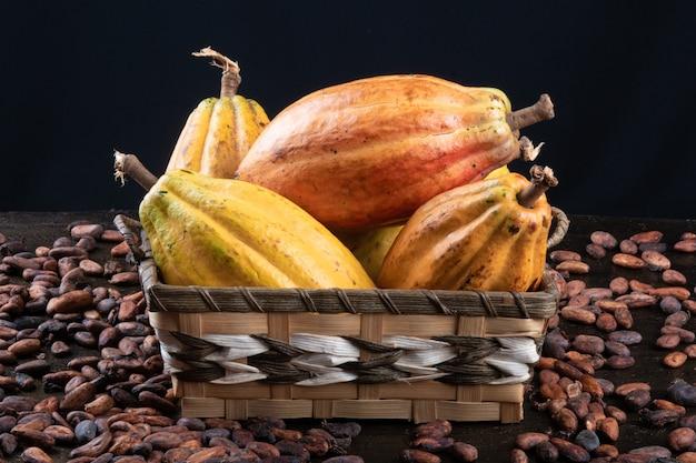 Owoce kakaowe i surowe ziarna kakaowe na stole z czarnym.