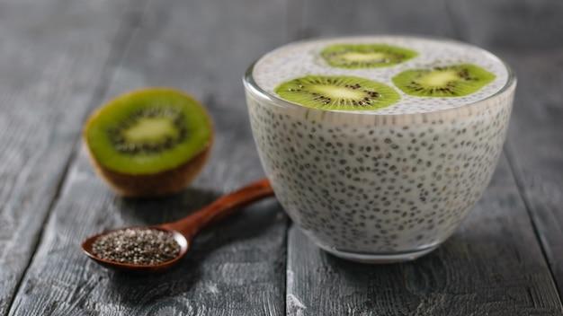 Owoce kiwi i szklana miska z nasionami chia z mlekiem i drewnianą łyżką na wiejskim stole.