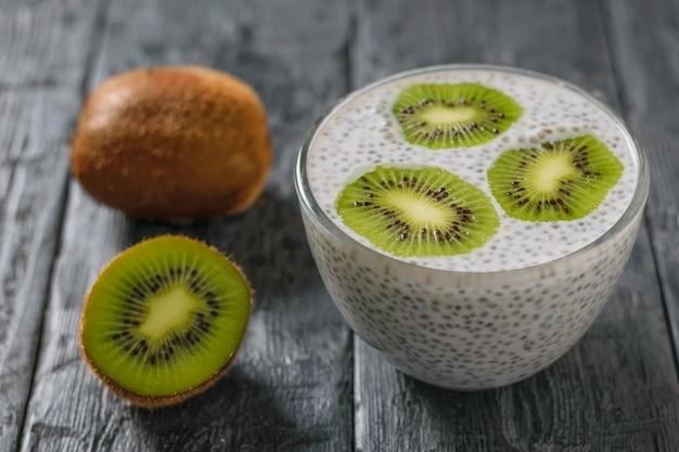 Owoce kiwi i szklana miska z nasionami chia z mlekiem na wiejskim stole.