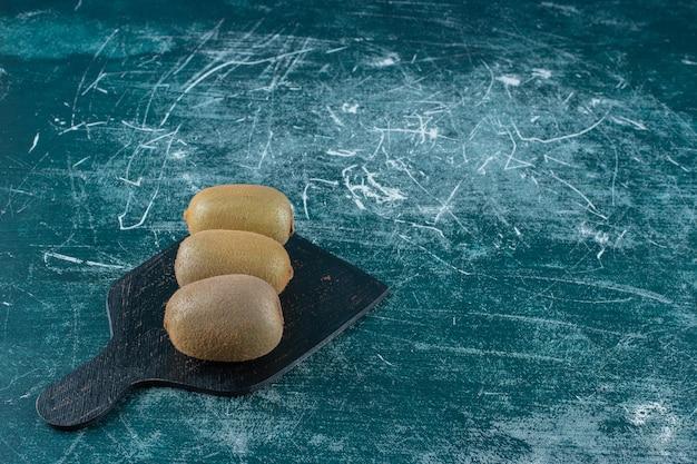 Owoce kiwi na desce do krojenia, na marmurowym stole.