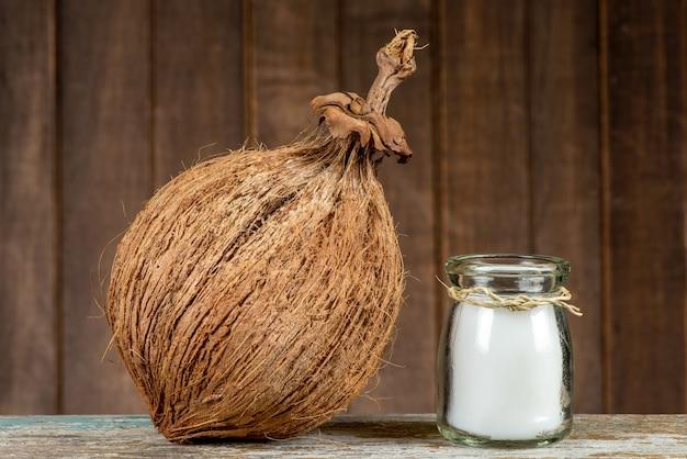 Owoce kokosowe i olej na tle starego drewna.