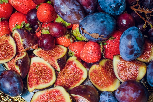 Owoce lata: melon, brzoskwinia, truskawki, jagody, jabłka, figi, wiśnie, morele, arbuzy i winogrona. różnorodność świeżych ekologicznych owoców na deser lub przekąskę. koncepcja zdrowej żywności.