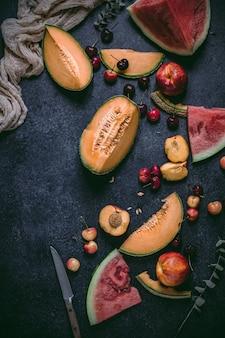 Owoce letnie, takie jak melon, czerwony arbuz, wiśnie na czarnej powierzchni.