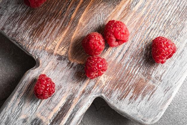 Owoce maliny na starej drewnianej desce do krojenia, zdrowy stos letnich jagód na kamiennej powierzchni betonowej, widok z góry