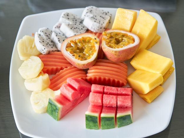 Owoce mieszane obejmują marakuję, zgrane mango, papaję, ananasy, smocze owoce i melon w talerzu na deser