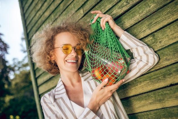 Owoce. młoda kobieta w okularach przeciwsłonecznych trzymająca siateczkową torbę z owocami