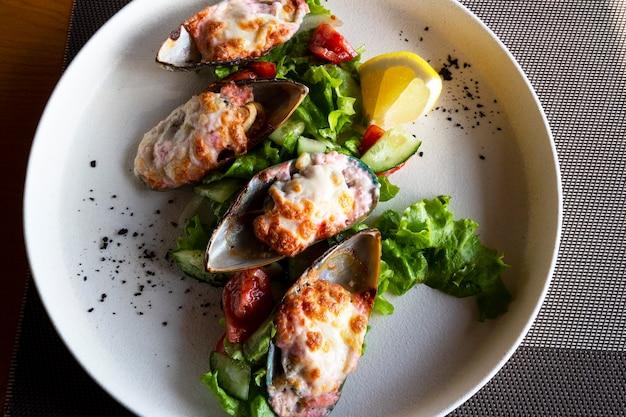 Owoce morza. małże z małży. pieczone małże w zielonej skorupce z serem, sałatą i cytryną na białym talerzu